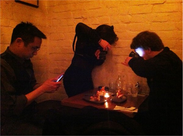 three-people-taking-pictures-of-their-food